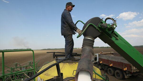 Механизатор загружает удобрения в бункер комбайна для обработки полей