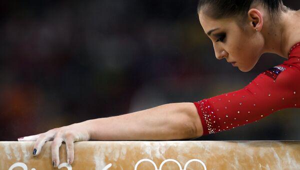 Алия Мустафина (Россия) выполняет упражнения на бревне в командном многоборье среди женщин на соревнованиях по спортивной гимнастике на XXXI летних Олимпийских играх