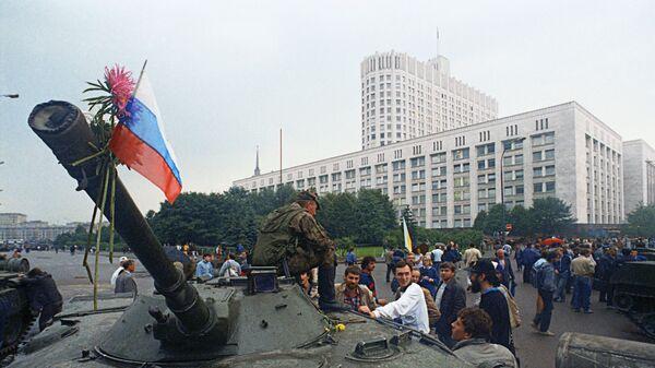 Защитники Белого дома прикрепили цветы к орудийному стволу одного из танков, введеных в Москву 19 августа 1991 года в связи с объявлением членами ГКЧП чрезвычайного положения в столице