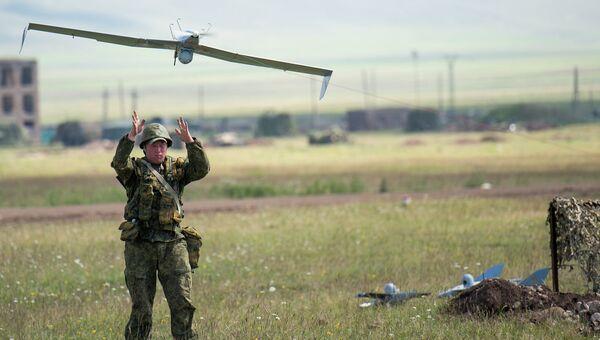 Военнослужащий запускает беспилотный самолет Тахион во время учений. Архивное фото