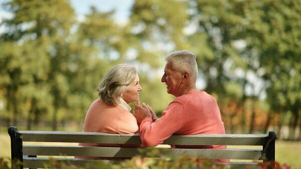Пожилая пара на скамейке в парке