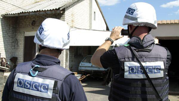 Представители ОБСЕ осматривают повреждения. Архивное фото