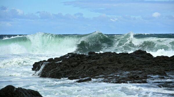 Волны Охотского моря у берега на западе острова Кунашир Большой Курильской гряды