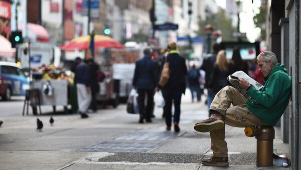 Мужчина читает газету на улице в Нью-Йорке, США. Архивное Фото.