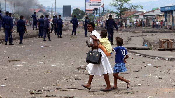 Семья на улице Киншасы во время столкновений представителей оппозиции и полиции. Архивное фото