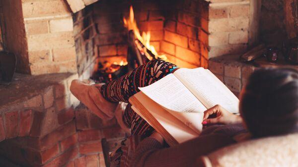 Девушка читает книгу у камина
