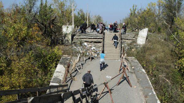 Жители идут по поврежденному мосту в районе пропускного пункта Станица Луганская в Донбассе