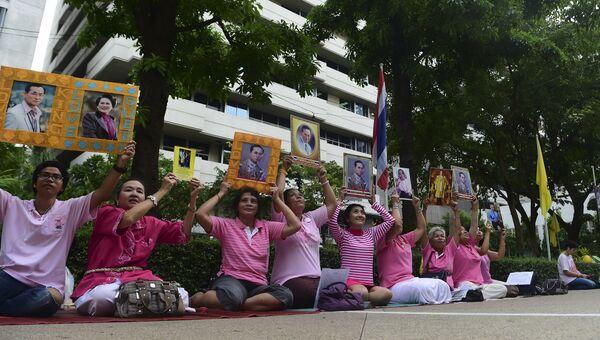 Женщины с портретами тайского короля Хумипхона Адулъядета у больницы в Бангкоке
