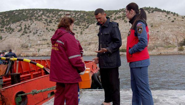 Сотрудницы скорой помощи и МЧС и один из спасенных членов экипажа плавучего крана, затонувшего у берегов Крыма, в порту Балаклавы. Архивное фото