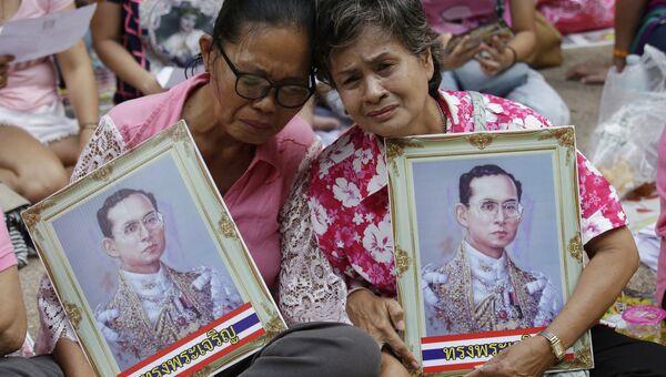 Женщины с портретами короля Таиланда Пхумипхона Адулъядета в Бангкоке. Архивное фото