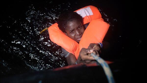 Мигрант во время спасательной операции недалеко от средиземноморского побережья Ливии. Архивное фото