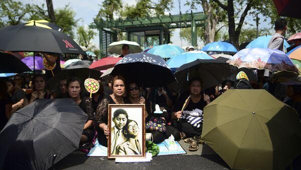 Люди на пути кортежа везущего тело короля Таиланда Пхумипона Адульядета в Бангкоке, Таиланд. 14 октября 2016. Архивное фото