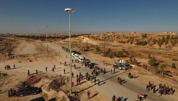 Сотрудники правоохранительных органов у автобусов и машин скорой помощи в районе гуманитарного коридора у трассы Кастелло на севере Алеппо в Сирии