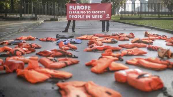 Люди держат плакат с надписью Европа не в состоянии защитить нуждающихся перед началом саммита ЕС в Брюсселе