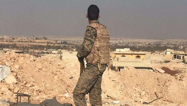 Боец сирийской армии смотрит на город Алеппо с высоты узла мобильной связи к югу от города.