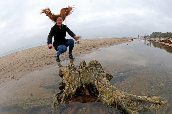 Девушка на берегу Балтийского моря, где вода отступила от берега на 20 метров, обнажив пни реликтовых деревьев