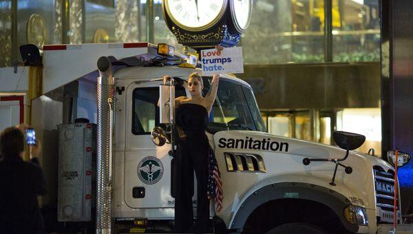 Певица Леди Гага с плакатом против кандидата в президенты США Дональда Трампа у башни Трампа в Нью-Йорке