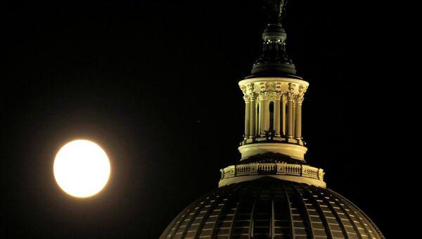 Луна поднимается над Капитолием накануне суперлуния в Вашингтоне, США. 13 ноября 2016
