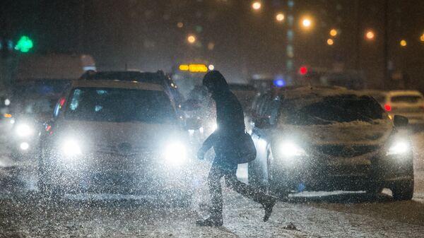 Прохожий переходит дорогу в Москве во время снегопада