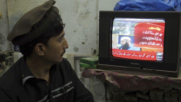 Мужчина смотрит новости о крушении пассажирского самолета недалеко от Хавелиана, Пакистан