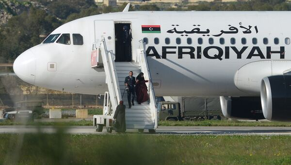 Пассажиры покидают самолет ливийской авиакомпании Afriqiyah Airways в аэропорту Мальты. 23 декабря 2016