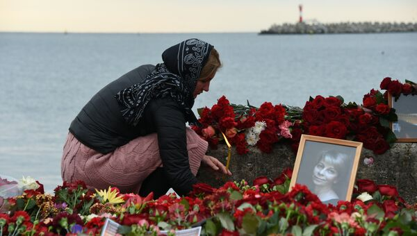 Женщина зажигает свечу в память о жертвах крушения самолета ТУ-154 в Сочи. Архивное фото