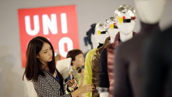 Девушка рассматривает одежду марки Uniqlo