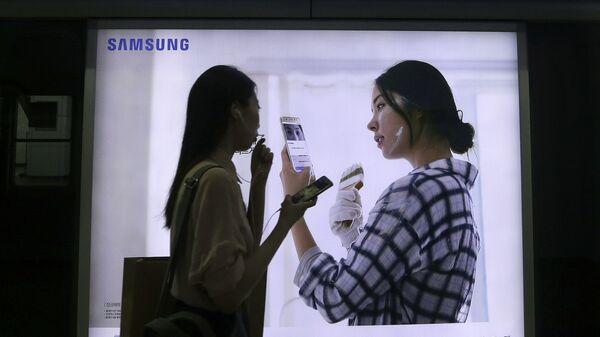 Девушка на фоне рекламы смартфона Galaxy Note 7 компании Samsung. Архивное фото