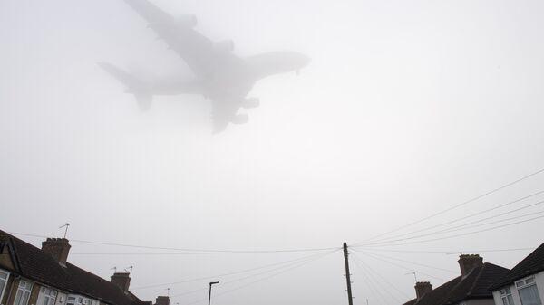 Самолет заходит на посадку в лондонском аэропорту Хитроу во время смога