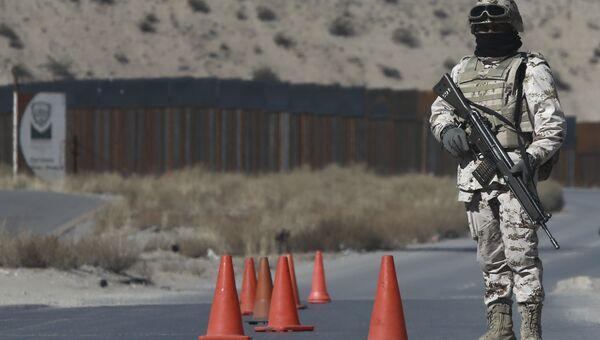 Мексиканский солдат на контрольно-пропускном пункте возле пограничного забора между Мексикой и США
