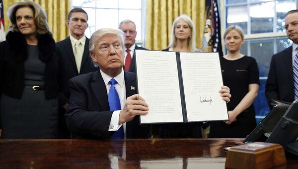 Президент США Дональд Трамп держит один из только что подписанных указов. 28 января 2017