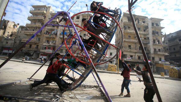 Дети качаются на качелях в разрушенном Алеппо, Сирия