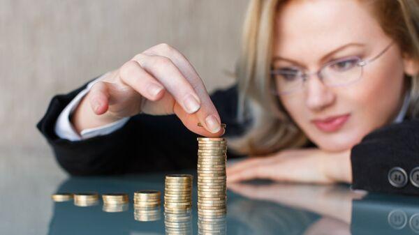 Женщина строит башню из монет