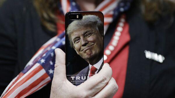 Женщина держит телефон с фотографией Дональда Трампа. Архивное фото