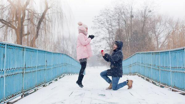 Молодой человек делает предложение руки и сердца своей девушке