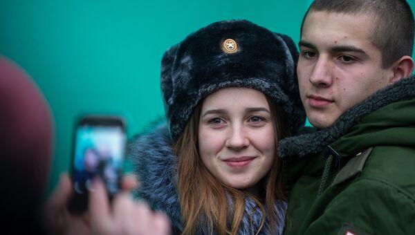 Призывник фотографируется с девушкой перед отправкой на службу в армию