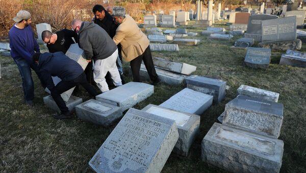 Местные жители устраняют послдствия акта вандализма на еврейском кладбище. Архивное фото