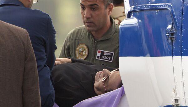Хосни Мубарак в сопровождении медицинского персонала у здания полицейской академии Каира перед заседанием суда по делу об убийстве демонстрантов в ходе январских беспорядков 2011 года. 2 марта 2017. Архивное фото