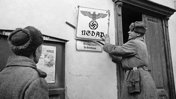 Советские бойцы - освободители Австрии от фашизма в селении Лекенгауз срывают вывески с фашистских учреждений