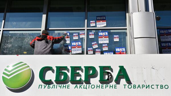 Рабочий очищает фасад центрального отделения дочернего предприятия Сбербанка России в Киеве от листовок