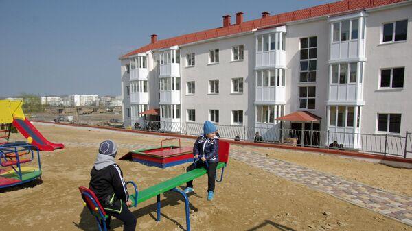Дети играют на детской площадке у новых домов в Крыму, построенных для переселенцев из зоны строительства Керченского моста
