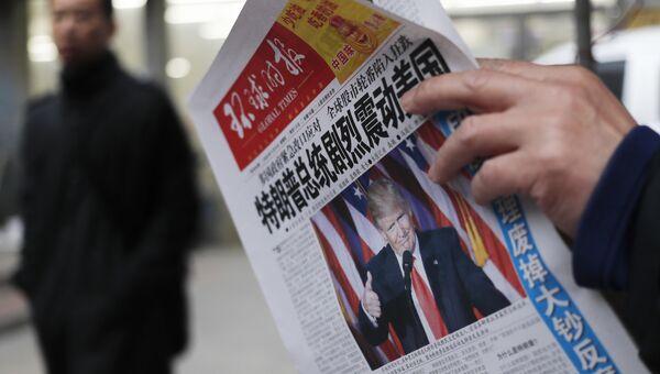 Мужчина в Китае читает газету с новостью об избрании Дональда Трампа президентом США. Архивное фото