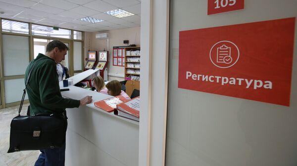 Посетитель у регистрационного стола. Архивное фото
