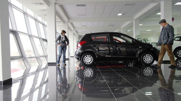 Посетители осматривают автомобиль в автосалоне. Архивное фото