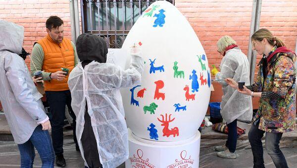 Участники расписывают пасхальные яйца на арт-фестивале для журналистов МедиаПасха в Москве