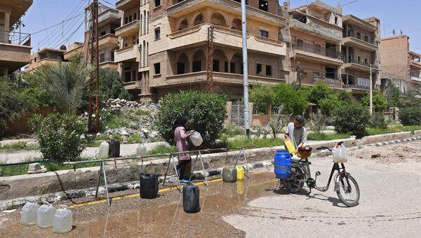 Жители набирают воду на улице в сирийском городе. Архивное фото