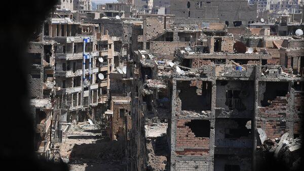Разрушенные здания района, контролируемого боевиками, в сирийском городе Дейр-эз-Зор. Архивное фото