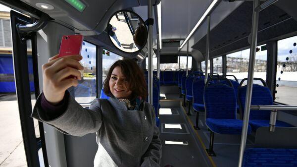 Девушка фотографируется в салоне нового электробуса в Москве