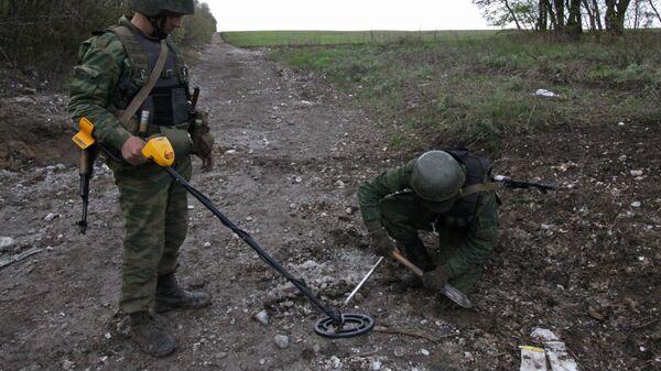 Саперы обследуют дорогу в районе подрыва автомобиля ОБСЕ возле села Пришиб в Луганской области. 25 апреля 2017