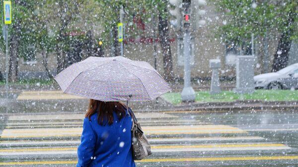 Женщина идет по улице Москвы во время снегопада